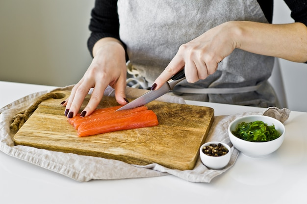 The chef cuts salmon fillets on a wooden chopping board.