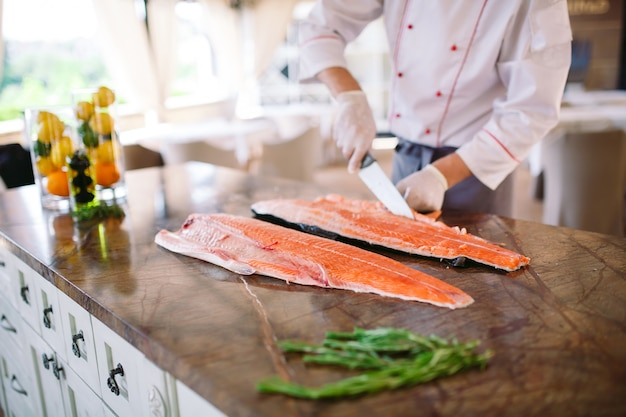 The chef cuts the salmon on the table.