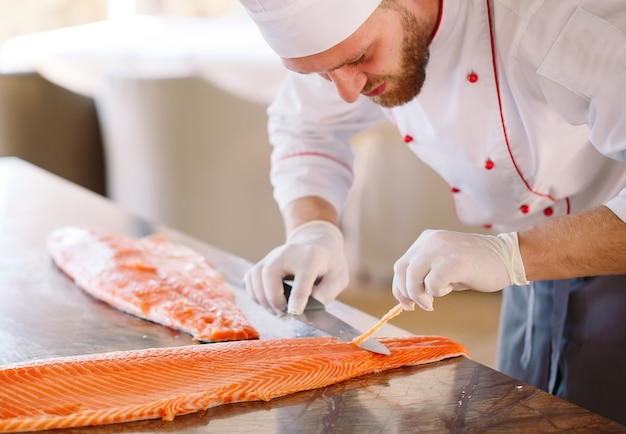 The chef cuts the salmon on the table
