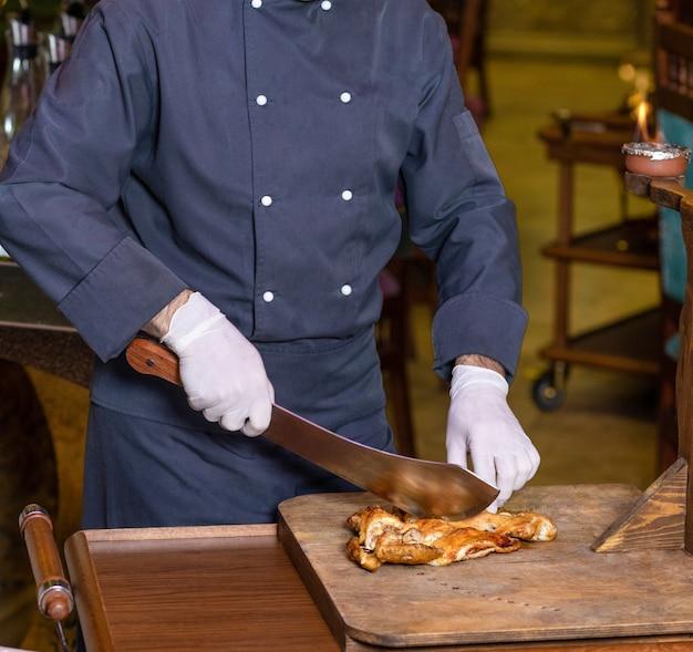 Шеф-повар режет куриное мясо тесаком на деревянной тарелке