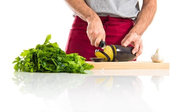 Chef tagliando una melanzana