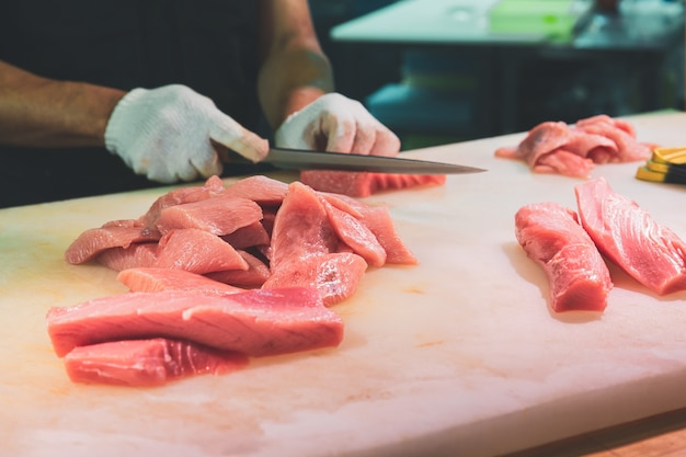 Chef cutting bluefin tuna in kuromon market