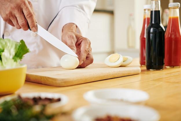 シェフが鶏の卵を切る