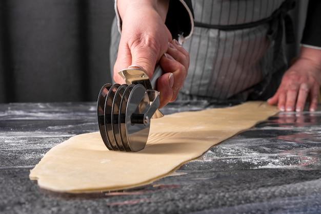 Chef cutting dough strips