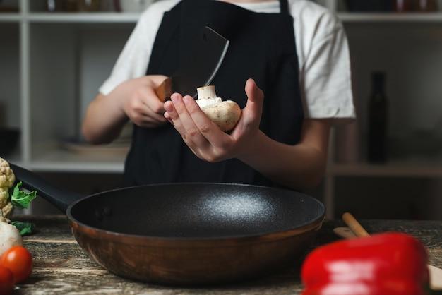 요리사가 요리를 위해 신선한 버섯을 자르고 있습니다. 요리사가 음식을 준비하고 있습니다. 어린이 요리사는 부엌에서 요리합니다. 요리사 앞치마와 모자를 쓴 소년. 나무 보드에 야채를 절단 하는 소년.