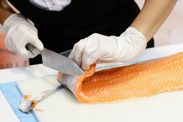 Chef cutting fresh salmon fillet in kitchen, chef cut the salmon