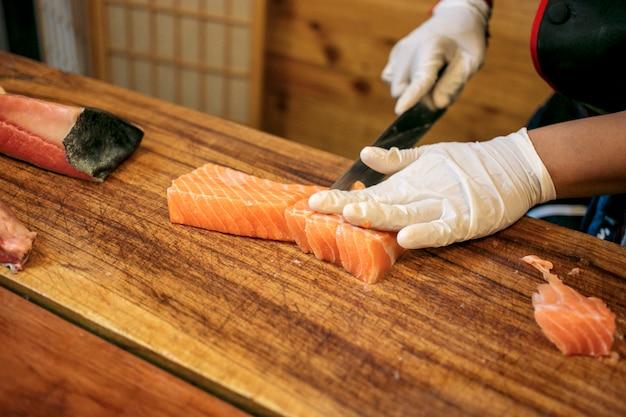 Chef cutting fresh salmon