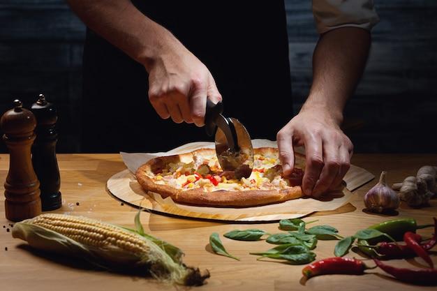 焼きたてのハワイアンピザを切るシェフ