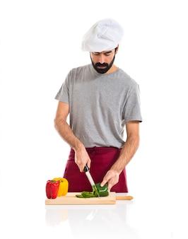 Шеф-повар, перерезающий зеленый перец