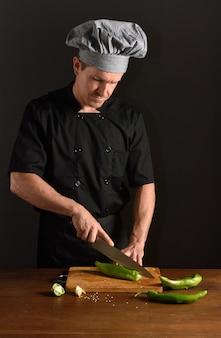 Chef cutting green pepper