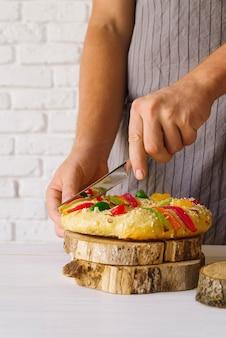 ナイフでひらめきの日のデザートに切り込むシェフ