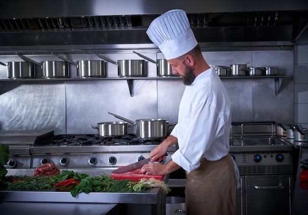 Chef cutting meat in restaurant kitchen
