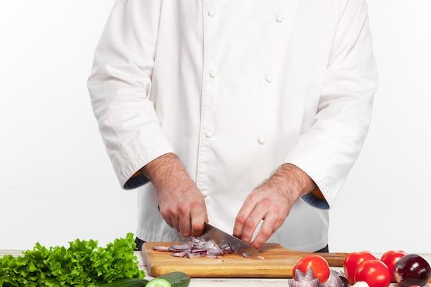 Cuoco unico che taglia una cipolla sulla sua cucina