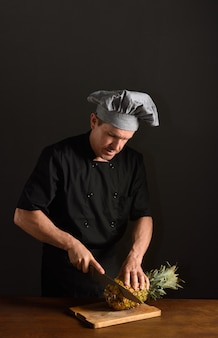 Chef cutting a pineapple
