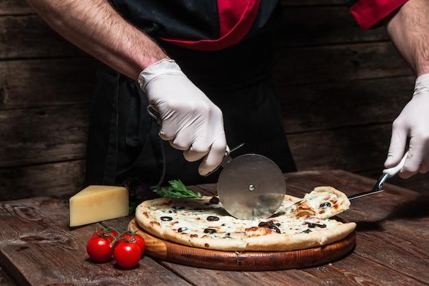 Шеф-повар режет кусок вкусной итальянской пиццы на деревенском деревянном столе.
