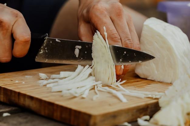 Повар режет нарезанную капусту