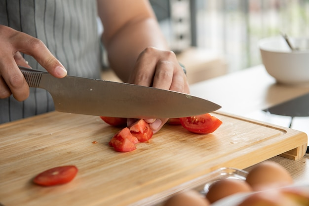Chef cutting tomatos on cutting board