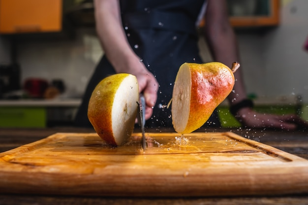 Chef cutting a yellow ripe pear in half with a large knife in motion
