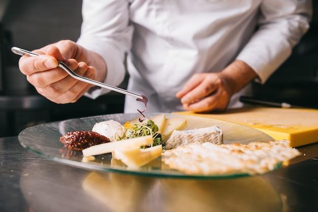Шеф-повар украшает сырную тарелку пинцетом