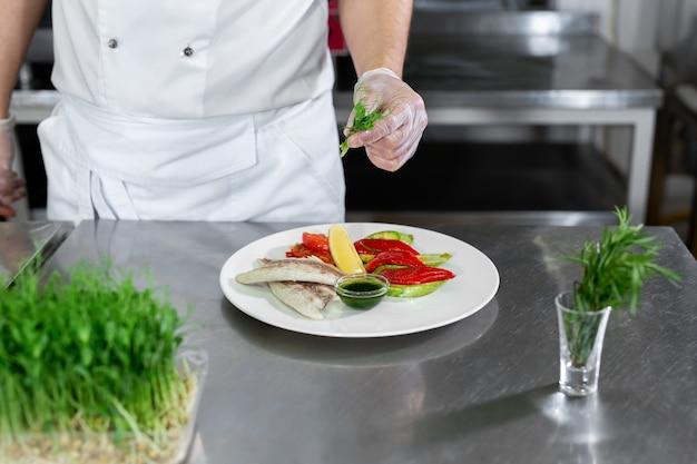 요리사는 야채와 함께 microgreens 물고기를 장식