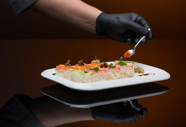 요리사는 캐비아로 스시를 장식합니다. 초밥을 만드는 과정