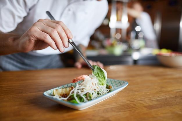 Шеф-повар украшает блюдо для гурманов крупным планом