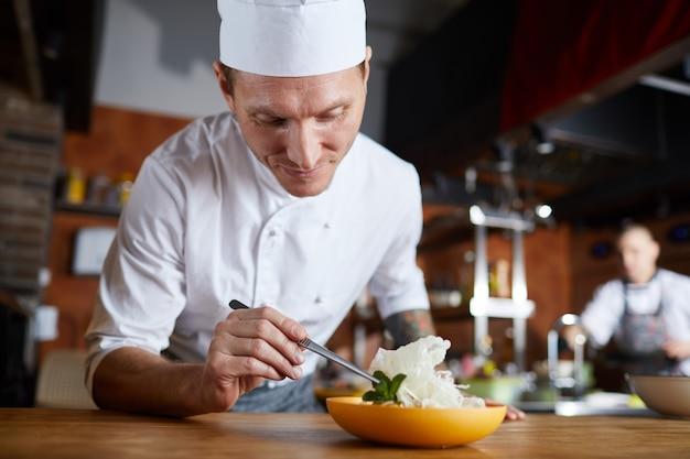 Шеф-повар украшает блюдо для гурманов