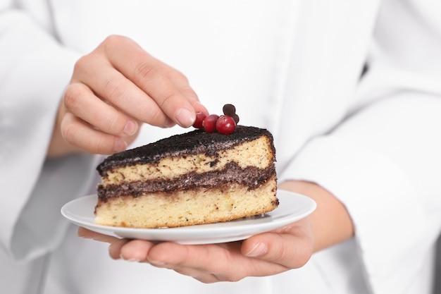 Шеф-повар украшая кусок вкусного шоколадного торта, крупным планом