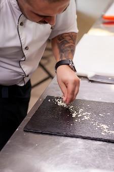 Шеф-повар делает прекрасный дизайн блюда на черной доске