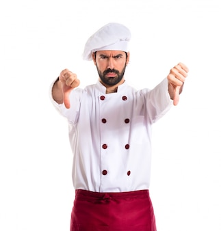 Chef doing a bad signal over white background