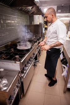 キッチンレストランで大きな火の炎で鍋にフランベを料理するシェフ