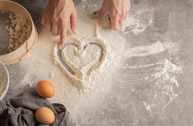 Chef drawing a heart in flour Premium Photo