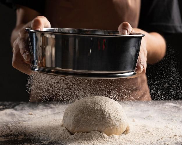 Повар посыпает мукой хлебное тесто