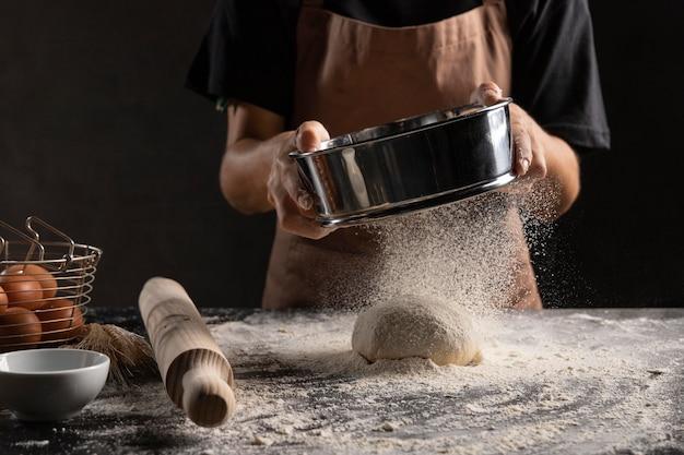 반죽 위에 밀가루를 뿌리는 요리사