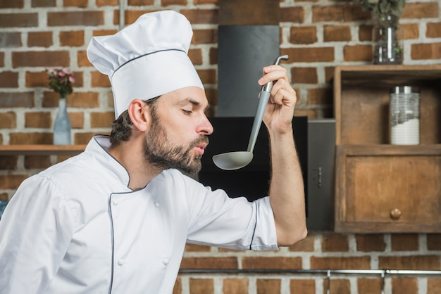 Chef enjoying the aroma of a soup in the ladle