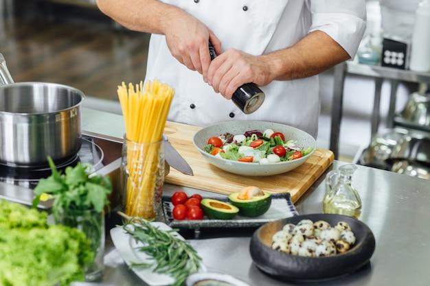 요리사가 그녀의 접시를 마무리하고 거의 테이블에서 봉사 할 준비가되었습니다.