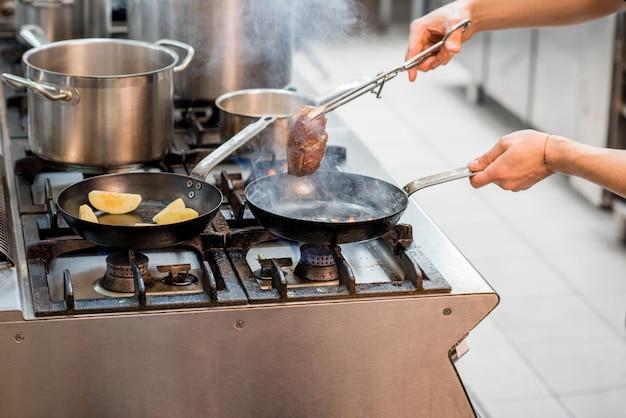 주방에 있는 가스레인지에서 요리사가 고기 스테이크를 굽고 있습니다. 프라이팬에 클로즈업 보기