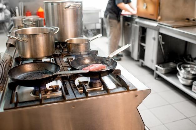 주방의 가스레인지에 고기 스테이크를 굽는 요리사