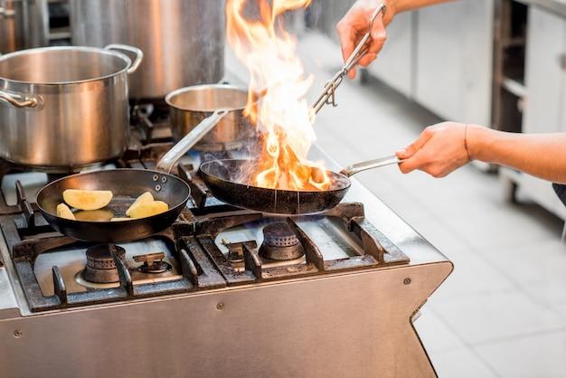 주방에서 가스레인지에 고기 스테이크를 굽고 있는 요리사. 프라이팬에 클로즈업 보기