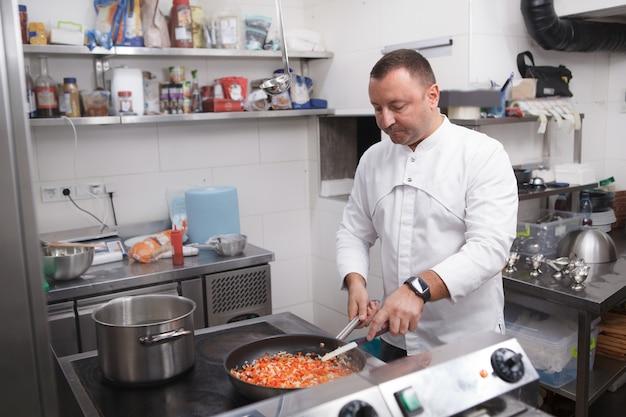 Шеф-повар, жарящий овощную смесь на сковороде, работает в ресторане, копирует пространство