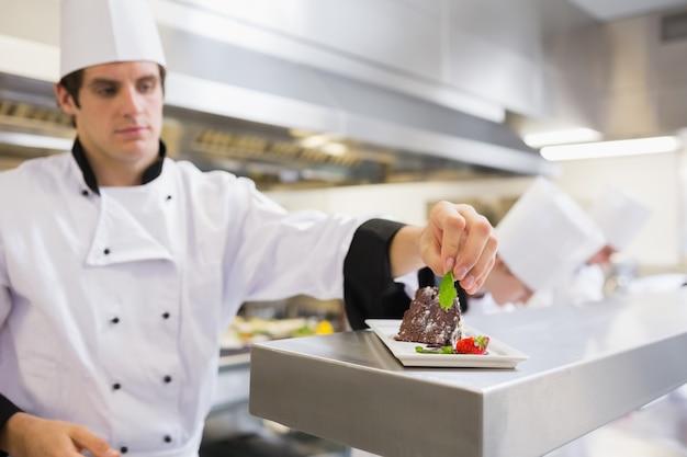 Chef garnishing his cake