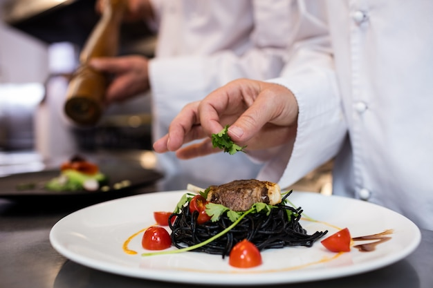 Chef garnishing meal on counter