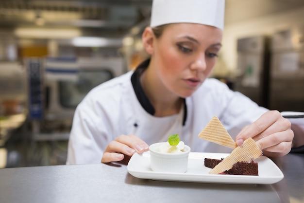 Chef garnishing a slice of cake
