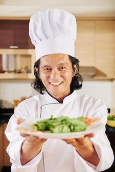 Шеф-повар дает тарелку салата