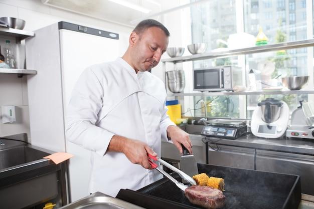 Шеф-повар готовит на гриле стейк из говядины и сладкую кукурузу на кухне, копия пространства