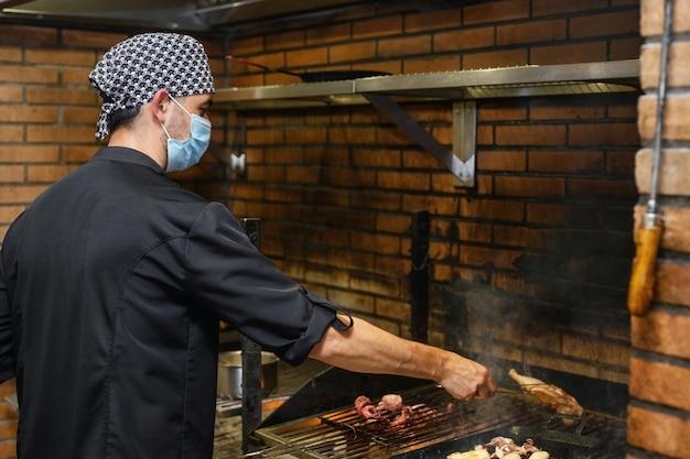 Шеф-повар готовит стейки на коммерческой кухне