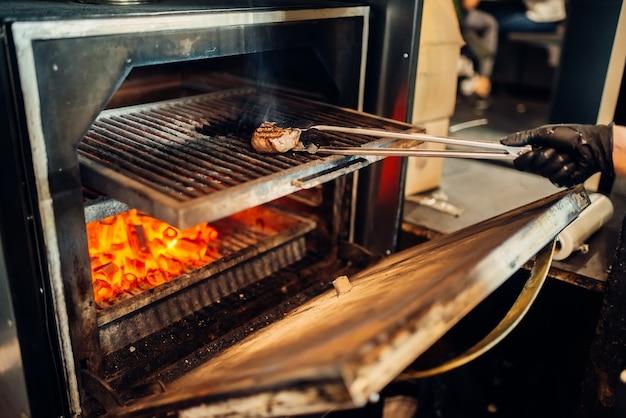 그릴 오븐에 스테이크를 준비하는 장갑에 요리사 손. 신선한 비프 스테이크 요리, 주방에서 음식 준비