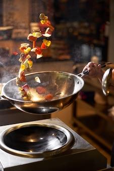 シェフの手が中華鍋を保ちます。クローズアップの手は、プロの暗いキッチンで食べ物を投げます。アジア料理を調理するシェフ。フードデリバリーコンセプト、ファーストフード