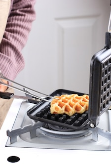 Chef hand take croffle from stove, preparation making croissant waffle or croffle from frozen croissant dough