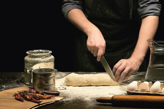Chef hands are cutting dough by knife on wooden table